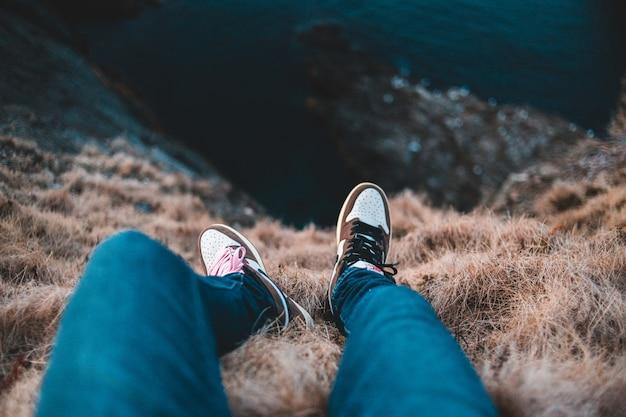 Person in blauen hosen und schwarzen und weißen turnschuhen, die tagsüber auf braunem grasfeld sitzen Kostenlose Fotos