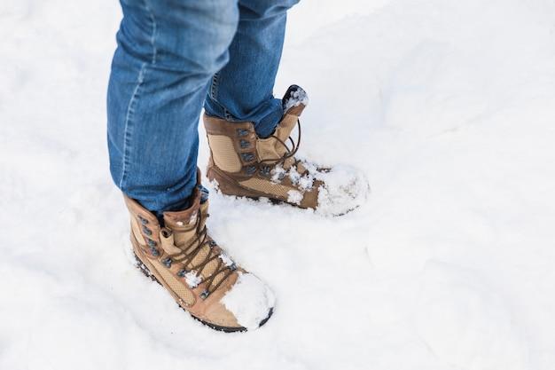 Person in stiefeln, die auf schnee stehen Kostenlose Fotos
