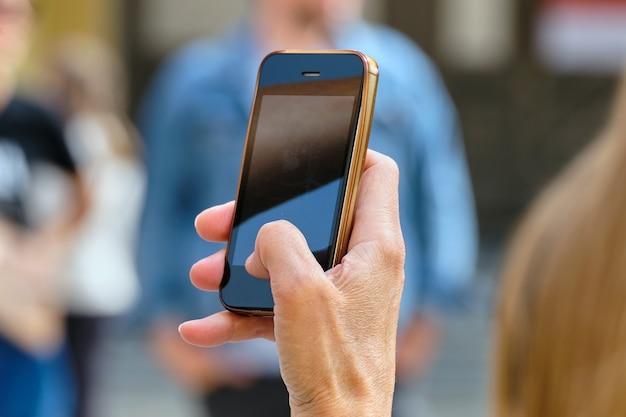 Person macht fotos auf ihrem smartphone auf der straße. Premium Fotos