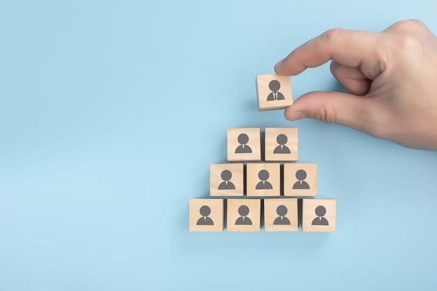 Personalpyramide. personalwesen, unternehmenshierarchiekonzept und mehrebenenmarketing - personalvermittler komplettieren das team, das durch einen holzwürfel von einer führungsperson vertreten wird. Premium Fotos