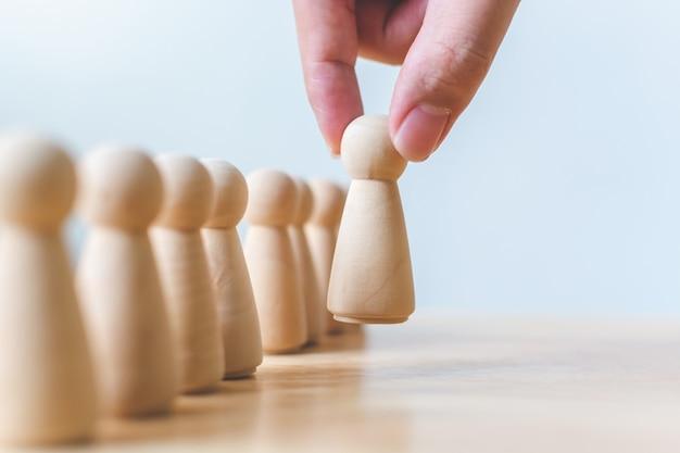 Personalwesen, talentmanagement, einstellungsangestellter, erfolgreiches geschäftsteamleiterkonzept. hand wählt hölzerne leute, die heraus von der masse stehen. Premium Fotos