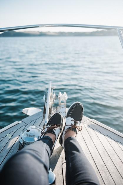 Personenfüße auf dem boot, das tagsüber auf dem meer segelt Kostenlose Fotos