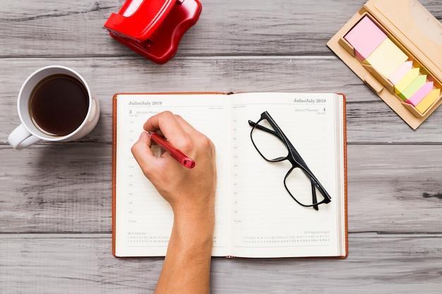 Personenschreiben auf notizbuch bei tisch Kostenlose Fotos