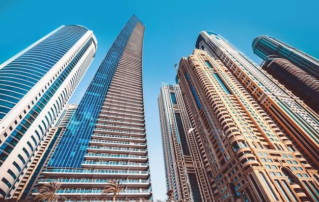 Perspektiven- und unterseitenwinkelansicht zum strukturierten hintergrund von modernen blauen gebäudeglaswolkenkratzern Premium Fotos
