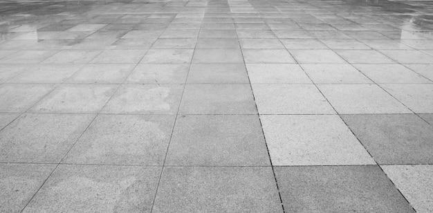 Perspektivenansicht von monotonem grey brick stone aus den grund für straßen-straße. bürgersteig, fahrstraße, straßenbetoniermaschinen, pflaster im weinlese-design, das quadratischen muster-beschaffenheits-hintergrund ausbreitet Premium Fotos