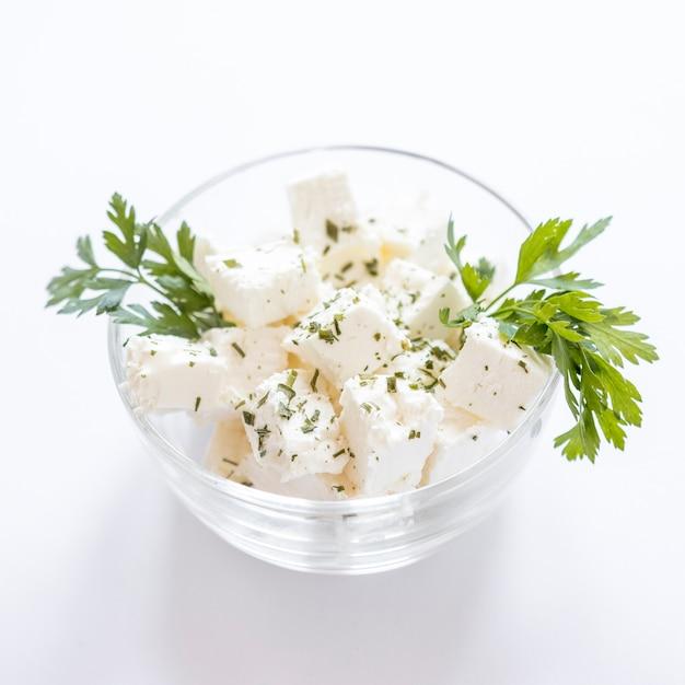 Petersilie mit käsewürfeln in der glasschüssel gegen weißen hintergrund Kostenlose Fotos