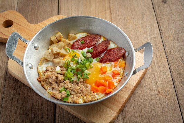 Pfanneneier mit chinesischer wurst, speckwürfeln und frühstück bestreut. Kostenlose Fotos
