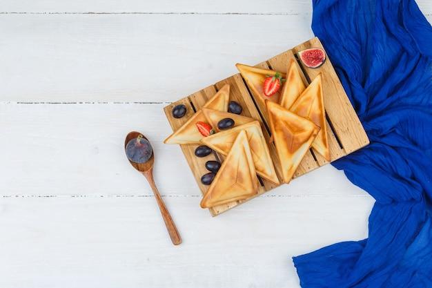 Pfannkuchen auf holzbrett mit holzlöffel und früchten Kostenlose Fotos