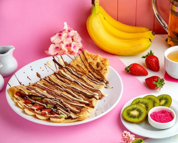 Pfannkuchen-crepes mit schokoladen-bananen-erdbeere und kiwi auf dem tisch Kostenlose Fotos