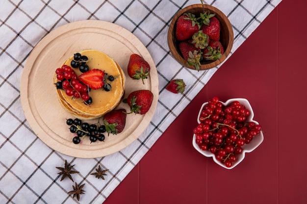 Pfannkuchen der draufsicht mit roten und schwarzen johannisbeeren und erdbeeren auf einem handtuch auf einem roten hintergrund Kostenlose Fotos