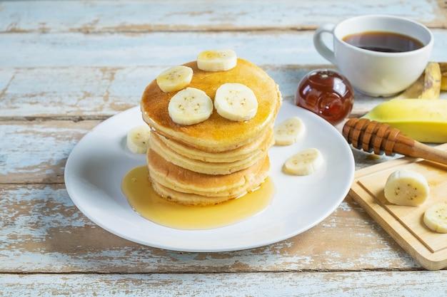 Pfannkuchen garniert mit honig und bananen auf dem tisch Premium Fotos