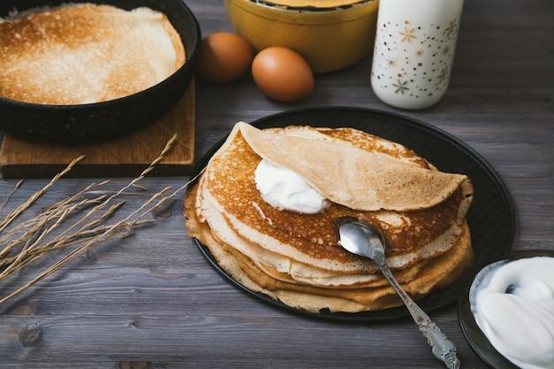 Pfannkuchen in einer bratpfanne und in bestandteilen für sie auf einem holztisch Premium Fotos