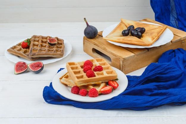 Pfannkuchen in weißem teller mit feigen und waffeln mit erdbeeren Kostenlose Fotos