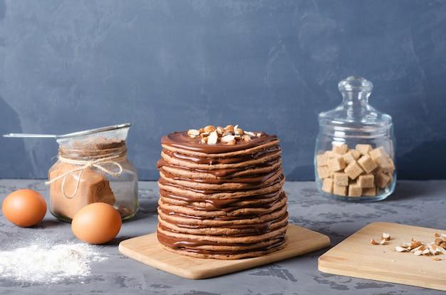 Pfannkuchen-kuchen. ein stapel schokoladenpfannkuchen mit schokoladencreme und -mandeln auf die oberseite. Premium Fotos