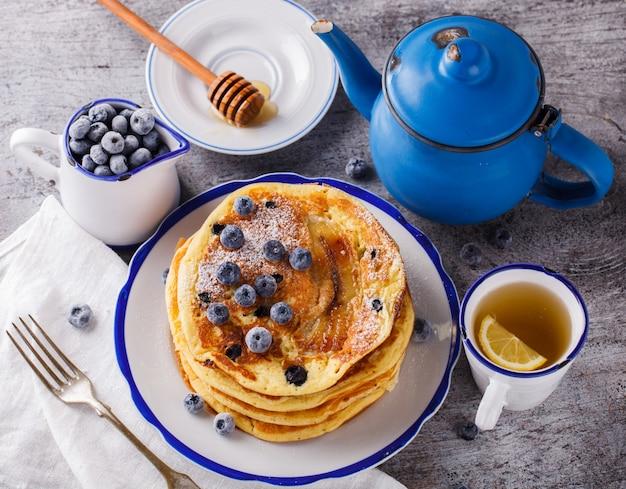 Pfannkuchen mit banane, blaubeeren und honig Premium Fotos
