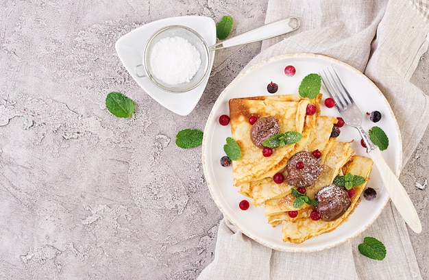 Pfannkuchen mit beeren und schokolade, dekoriert mit minzblatt Premium Fotos