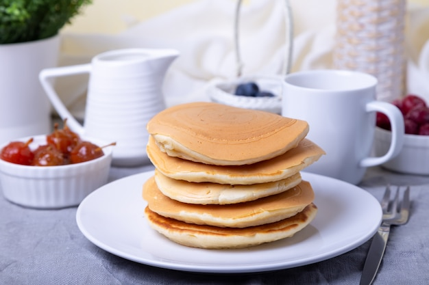 Pfannkuchen mit blaubeeren, kirschen und mini-apfelmarmelade. eine tasse kaffee und soßenboot im hintergrund. traditionelle amerikanische pfannkuchen. nahansicht. Premium Fotos