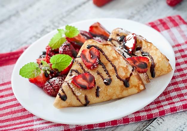 Pfannkuchen mit erdbeeren und schokolade mit minzblatt verziert Kostenlose Fotos