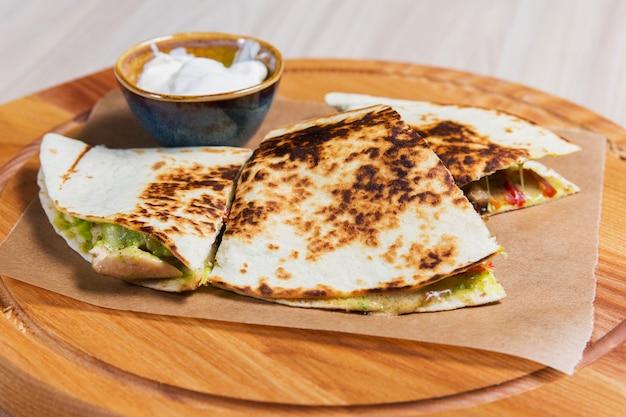 Pfannkuchen mit gemüse und weißer soße auf holztisch in einem restaurant. gesundes essen Premium Fotos
