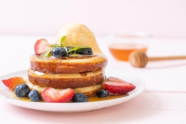 Pfannkuchen mit heidelbeeren, erdbeeren, honig und vanilleeis Premium Fotos