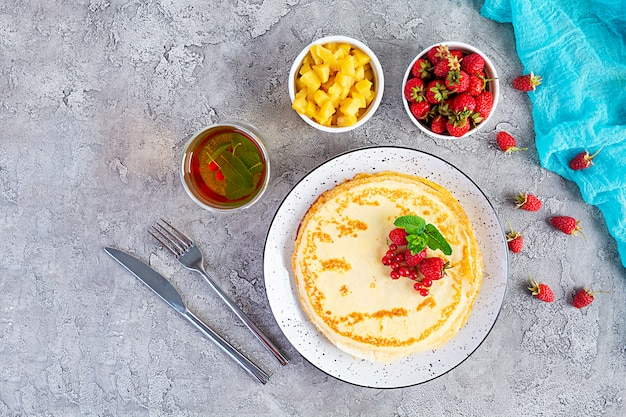 Pfannkuchen mit karamellisierten äpfeln, himbeeren, erdbeeren und roten johannisbeeren Premium Fotos