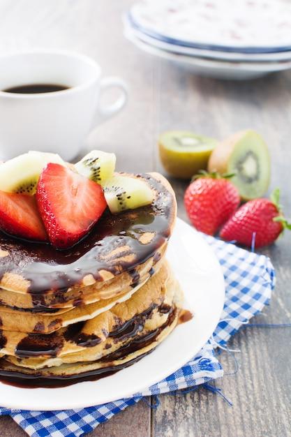 Pfannkuchen mit schokolade, erdbeeren und kiwi auf holztisch Premium Fotos