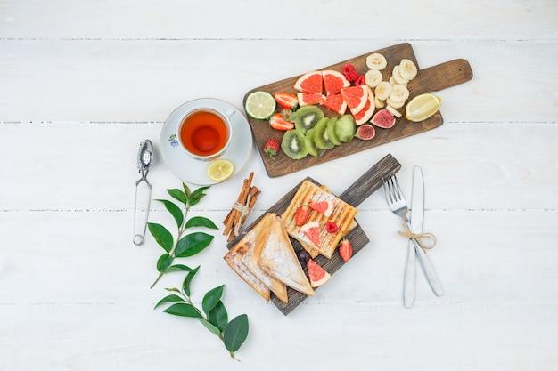 Pfannkuchen und waffeln auf holzbrett mit tee und obst Kostenlose Fotos
