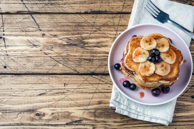 Pfannkuchenkuchen mit bananen und beerensirup, selektiver fokus, dunkler hintergrund. platz kopieren Premium Fotos