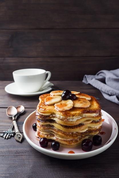 Pfannkuchenkuchen mit bananen und beerensirup, selektiver fokus, dunkler hintergrund. Premium Fotos
