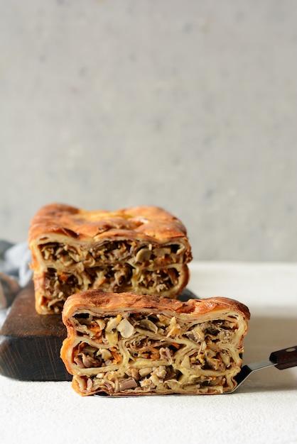Pfannkuchentorte mit fleisch und pilzen. pfannkuchen-kuchen in form von brot. slawische küche. pfannkuchentorte mit fleisch und pilzen Premium Fotos