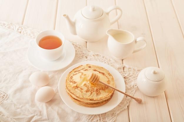 Pfannkuchenwoche: pfannkuchen mit honig und tee auf dem tisch Premium Fotos