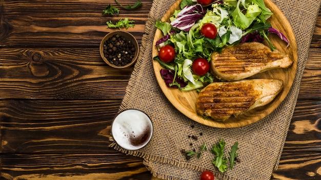 Pfeffer und bier in der nähe von salat und hühnchen Kostenlose Fotos