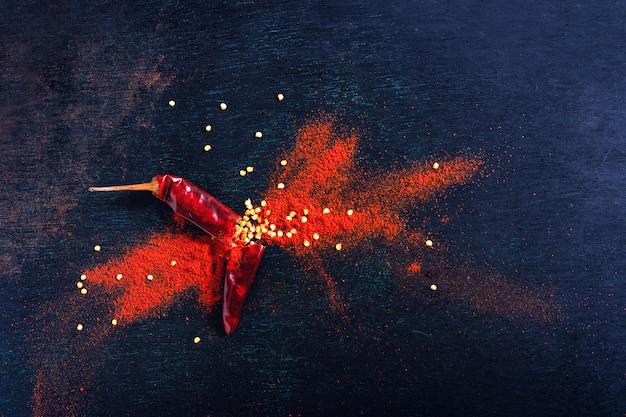 Pfefferflocken des roten paprikas und chilipulver sprengten auf schwarzem hintergrund Premium Fotos