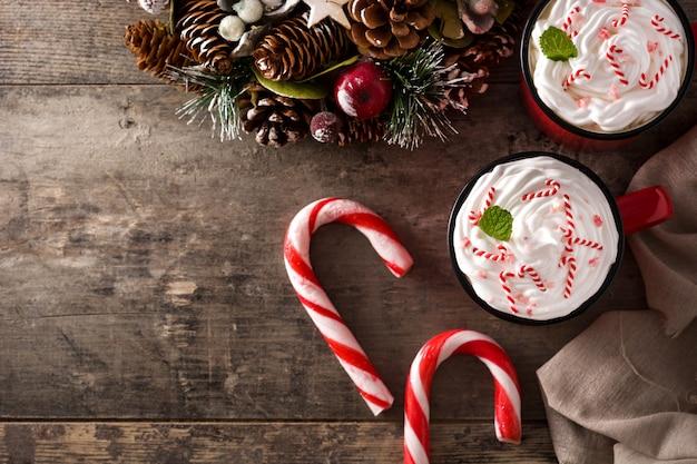 Pfefferminzkaffeemokka verziert mit zuckerstangen für weihnachten auf holztisch Premium Fotos