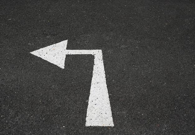 Pfeil links abbiegen markierungszeichen auf der neuen asphaltstraße. Premium Fotos