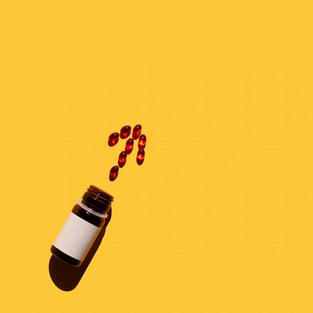 Pfeil von vitaminen, verschüttend aus einer flasche auf gelbem hintergrund heraus. ansicht von oben. Premium Fotos
