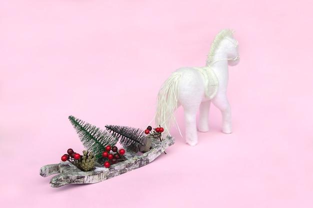 Pferd trägt schlitten mit weihnachtsbäumen, zapfen, bällen Premium Fotos