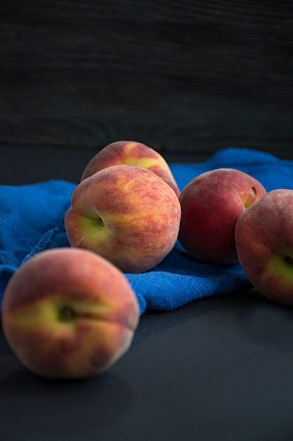 Pfirsiche auf dunkler oberfläche Premium Fotos