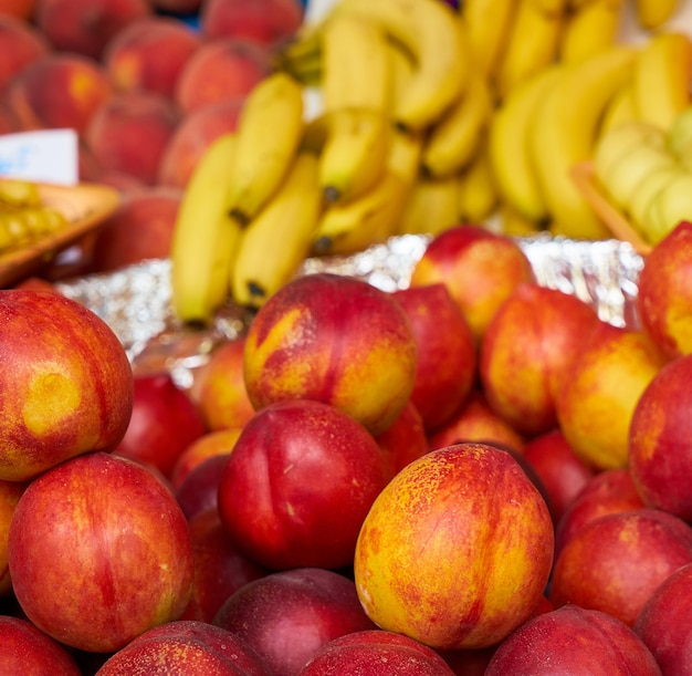 Pfirsiche mit bananen im hintergrund Kostenlose Fotos