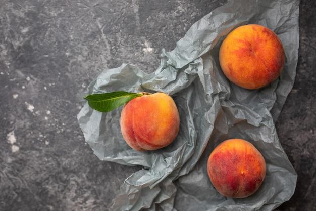 Pfirsiche oder nektarinen in einer grauen dunklen steinplatte mit blättern, draufsicht Premium Fotos