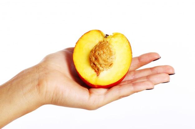 Pfirsichfrucht in der hand der frau Kostenlose Fotos