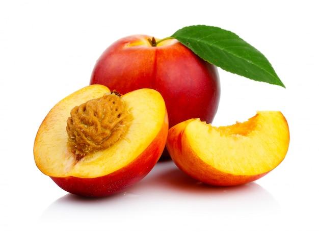 Pfirsichfrüchte mit den scheiben- und grünblättern getrennt Premium Fotos