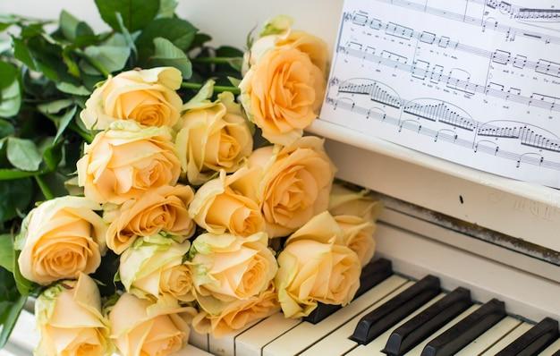 Pfirsichrosen auf dem klavier mit anmerkungen Premium Fotos