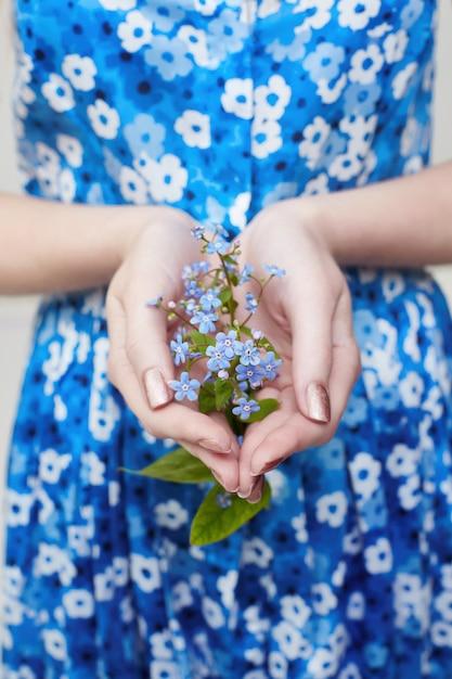 Pflanze mit blumen in der hand des mädchens. ökologie Premium Fotos