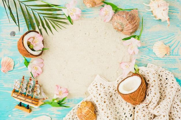 Pflanzenblätter in der nähe von kokosnüssen und blumen mit muscheln an bord Kostenlose Fotos