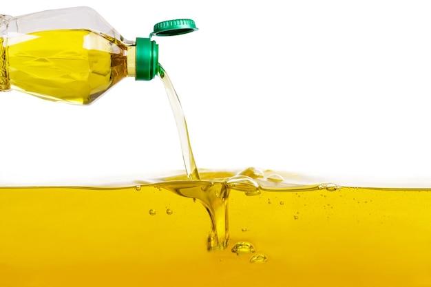 Pflanzenöl, das auf pflanzenölhintergrund gießt Premium Fotos