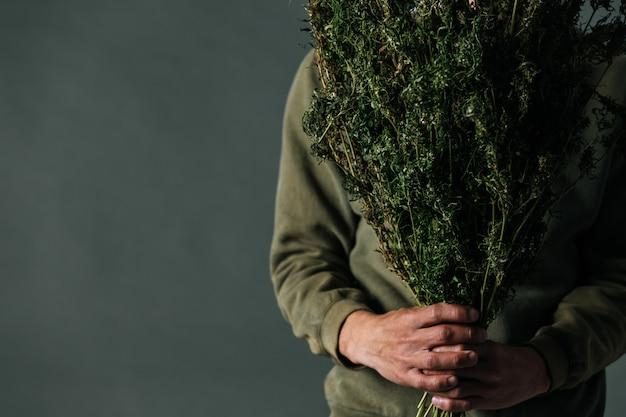 Pflanzer halten cannabisbäume auf einem grauen hintergrund. Kostenlose Fotos