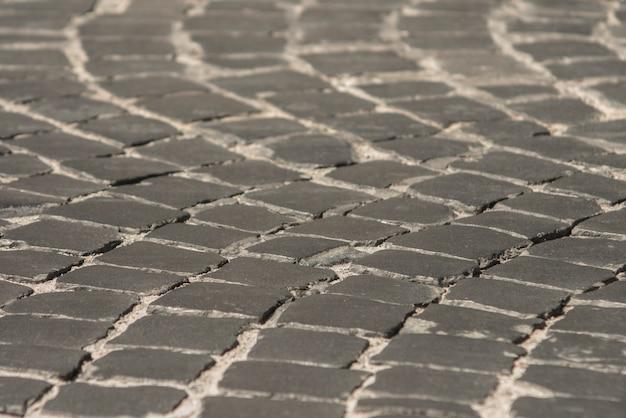 Pflasterung in der alten stadt des schwarzen kopfsteins. hintergrundtextur Premium Fotos