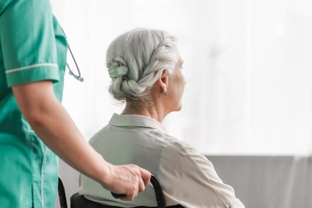 Pflegekraft mit älterem weiblichem patienten im rollstuhl Kostenlose Fotos