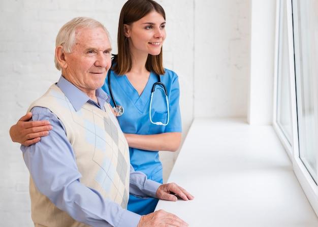 Pflegekraft und alter mann, die auf dem fenster schauen Kostenlose Fotos